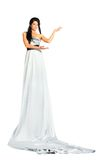 Woman wearing very long silver dress stands. Beautiful woman wearing very long silver dress stands and depicts beautiful figure by hands isolated on white Royalty Free Stock Photography