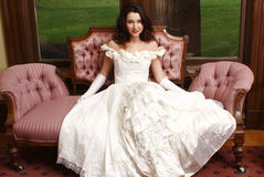 Woman wearing vintage dress. Sitting on antique sofa Stock Photos
