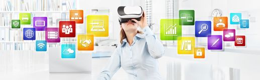 Woman wearing virtual reality glasses in office, with colors ico Stock Photo