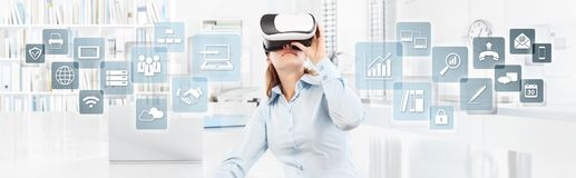 Woman wearing virtual reality glasses in office, with icons, web Royalty Free Stock Image