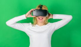 Woman wearing virtual reality goggles in green background. Happy woman exploring augmented world, interacting with. Digital interface. Woman using VR device royalty free stock photos