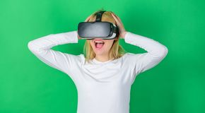 Woman wearing virtual reality goggles in green background. Woman with virtual reality headset. Confident young woman. Adjusting her virtual reality headset and royalty free stock images