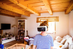 Woman wearing virtual reality goggles standing in living room Royalty Free Stock Photography