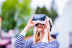 Woman wearing virtual reality goggles in the street Royalty Free Stock Image