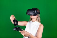 Woman wearing virtual reality headset with handheld  controllers. Attractive woman wearing virtual reality headset with two handheld trackpads or controllers in Royalty Free Stock Photos