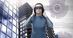 Woman wearing virtual reality headset and Tall buildings with sci-fi interface background. Digital composite of Woman wearing virtual reality headset and Tall Stock Photos