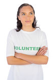 Woman wearing volunteer tshirt with arms crossed while looking upwards Royalty Free Stock Photo