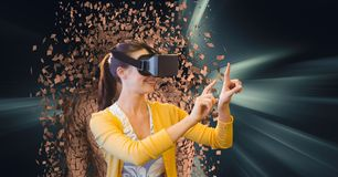 Woman wearing VR glasses with 3d scattered human figure in background. Digital composite of Woman wearing VR glasses with 3d scattered human figure in background Royalty Free Stock Images