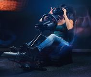 Woman wearing VR headset driving on car racing simulator cockpit with seat and wheel. Young woman wearing VR headset driving on car racing simulator cockpit royalty free stock images