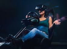 Young woman wearing VR headset having fun while driving on car racing simulator cockpit with seat and wheel. Woman wearing VR headset having fun while driving stock images