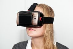 Woman wearing VR-headset over white background Royalty Free Stock Images