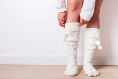 Woman wearing warm socks close-up. Woman`s legs wearing warm socks close-up. Cozy winter clothing stock photo