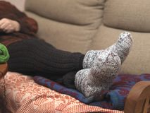 Feet In Wool Socks. Woman wearing warm wool socks and stockings relaxing or sleeping on the sofa Royalty Free Stock Image