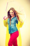 Woman wearing waterproof coat under umbrella Royalty Free Stock Photography