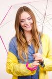 Woman wearing waterproof coat under umbrella Stock Images
