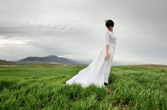 Woman wearing a wedding dress in the meadow. Woman wearing a wedding dress in the field in Granada, Andalusia, Spain Royalty Free Stock Images