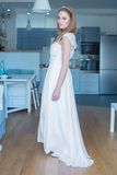 Woman Wearing Wedding Dress Standing in Kitchen. Woman Wearing White Wedding Dress Standing in Kitchen and Looking Over Shoulder at Camera Royalty Free Stock Photo