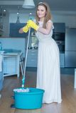 Woman Wearing Wedding Gown with Mop and Bucket Stock Images