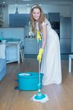 Woman Wearing Wedding Gown Mopping Floor. Woman Wearing White Wedding Gown Mopping Floor in Kitchen Royalty Free Stock Image