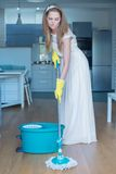 Woman Wearing Wedding Gown Mopping Floor. Woman Wearing White Wedding Gown Mopping Floor in Kitchen and Making Sour Face Royalty Free Stock Photo