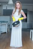 Woman Wearing Wedding Gown Washing Pan in Kitchen Royalty Free Stock Photography