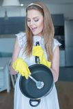 Woman Wearing Wedding Gown Washing Pan in Kitchen Stock Photography