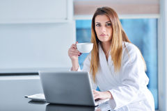 Woman wearing a white bathrobe with laptop Royalty Free Stock Image
