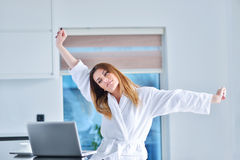 Woman wearing a white bathrobe with laptop Royalty Free Stock Photo