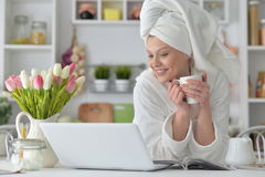 Woman wearing a white bathrobe with laptop Royalty Free Stock Photos