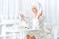 Woman wearing a white bathrobe with laptop Royalty Free Stock Images