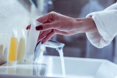 Woman wearing white bathrobe with red nails taking her face cream. Face cream. Young woman wearing white bathrobe with red nails taking her face cream after royalty free stock images