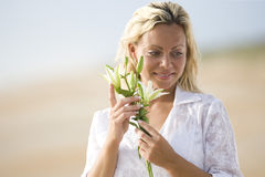 Woman wearing white on beach holding flower Stock Images