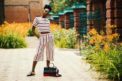 Woman Wearing White, Black, and Red Striped Crew-neck T-shirt With Matching Pants Standing Outside Beside Black Leather 2-way Bag stock images
