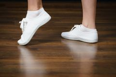 Woman wearing white bright sneakers trainers. Unrecognizable woman wearing white bright sneakers trainers and socks standing on shiny wooden floor Stock Photo