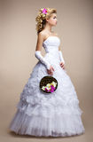 Wedding Style. Bride wearing White Dress and Gloves. Trendy Bouquet of Flowers stock images