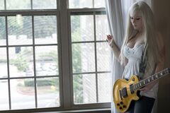Woman Wearing White Dress Holding Electric Guitar Stock Photos