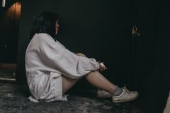 Woman Wearing White Dress Shirt and White Shoes Sitting on Black Flooring Stock Photography