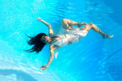 Woman wearing a white dress underwater Stock Images