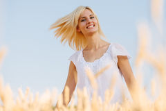 Woman wearing white dress, in wheat field during summer day. Royalty Free Stock Image
