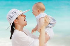 Woman Wearing White Hat Holding Baby Wearing White Onesie Near Beach during Day Time Stock Image