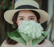 Woman Wearing White Hat Holding Flowers Stock Photos