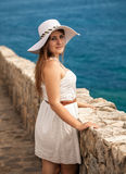 Woman wearing white hat posing on stone wall at seaside castle Stock Photo