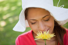 Woman wearing a white hat while smelling a flower with her eyes Royalty Free Stock Photography