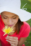 Woman wearing a white hat while smelling a flower while looking Stock Image
