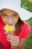 Woman wearing a white hat while smelling a flower while looking Royalty Free Stock Photo