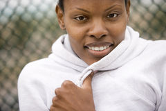Woman wearing white hooded sports top, smiling, front view, close-up, portrait Royalty Free Stock Image