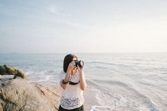 Woman Wearing White Lace Shirt Holding Black Digital Camera Standing on Rock Formation Near Body of Water Stock Photography