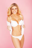 Woman wearing white lingerie on a pink background Stock Image