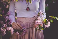 Woman Wearing White Long Sleeve Shirt and Beige Skirt Holding Pink Petaled Flower Royalty Free Stock Photo