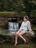 Woman Wearing White Long Sleeve Shirt Sitting Near Waterfalls Stock Image